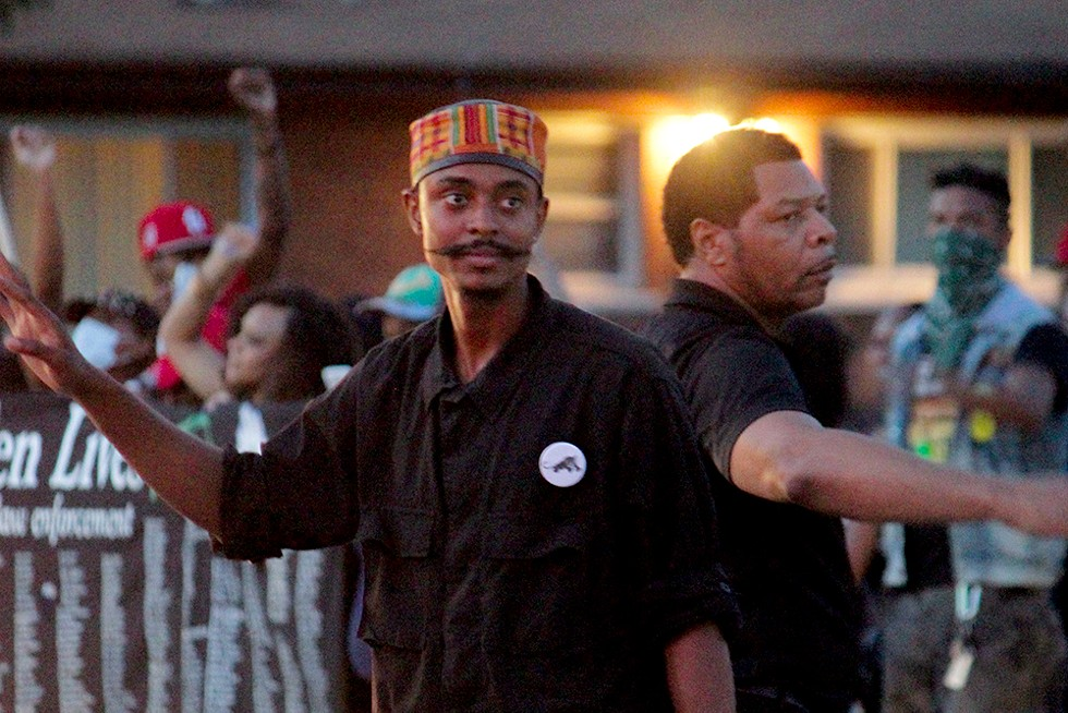In this image from August 14, 2014, Davis and other members of the New Black Panthers helps direct traffic during a demonstration. - DANNY WICENTOWSKI