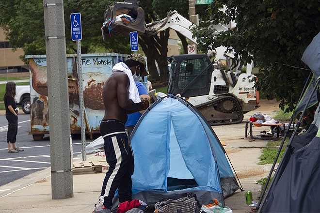 An unhoused resident of Interco Plaza gathers the contents of his tent as city workers clear the encampment. - DANNY WICENTOWSKI
