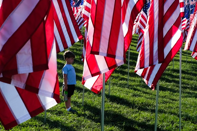 """A small boy stands among the rows of flags on Art Hill during the """"Flags of Valor"""" memorial. - PHUONG BUI"""