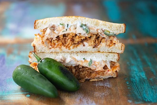 Chicken popper sandwich with shredded chicken, garlic, jalapeños, cream cheese, provolone and crispy onions. - MABEL SUEN