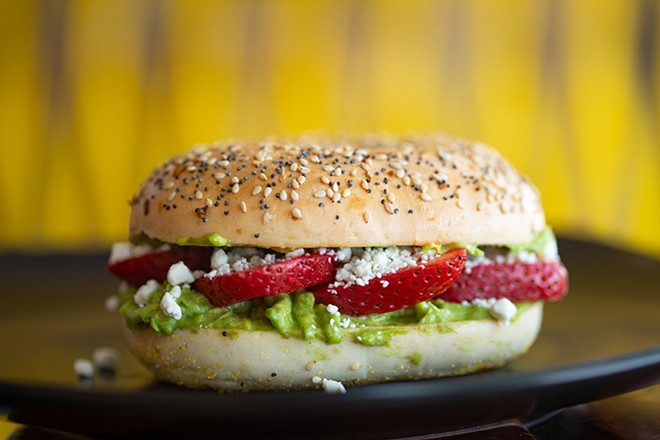 Avogoa bagel with avocado spread, goat cheese and strawberries on a toasted everything bagel. - MABEL SUEN