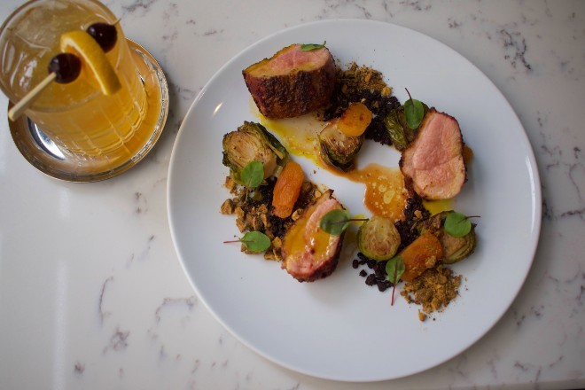 Tandoor duck breast, Corrigan's favorite entree, features Brussels confit, apricot, cocoa soil and black lime pistachio. - CHERYL BAEHR