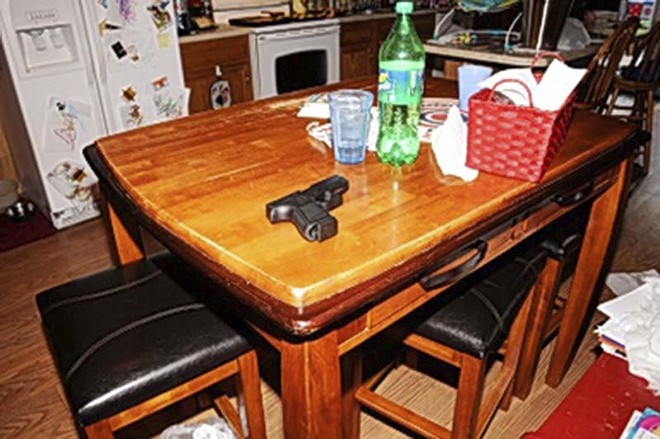 Lasley's gun, photographed as evidence on the family's kitchen table after the shooting. - COURTESY OF ST. LOUIS COUNTY POLICE
