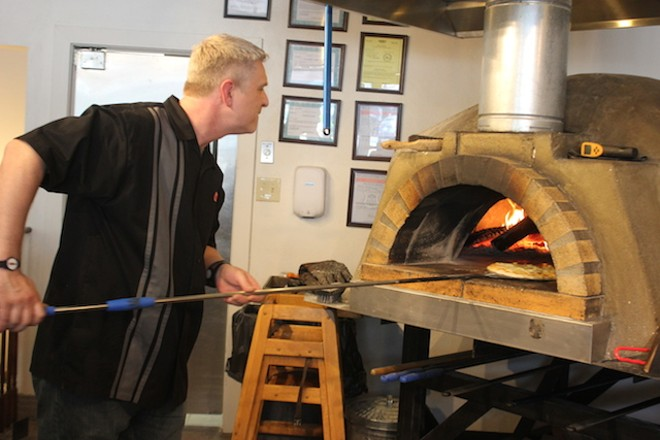 Ryan Reel works the pizza oven, which easily climbs to 800 degrees during a shift. - PHOTO BY SARAH FENSKE
