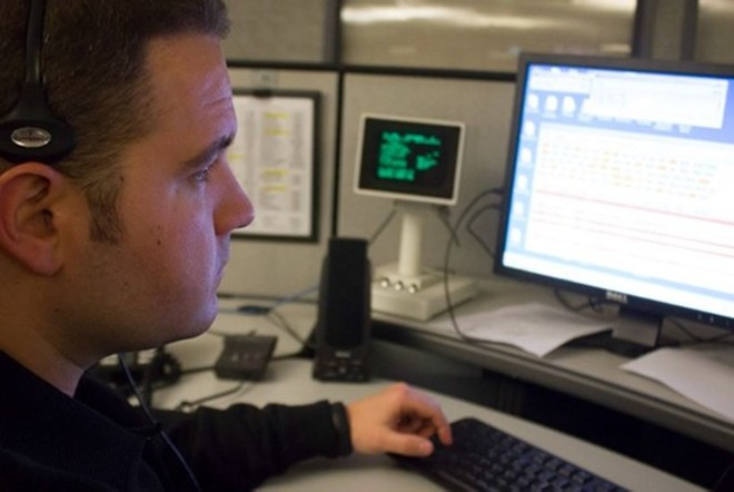 911 dispatchers in St. Louis city and county, like the staffer above, use encrypted transmissions. Springfield? Not so much. - PHOTO BY DANNY WICENTOWSKI