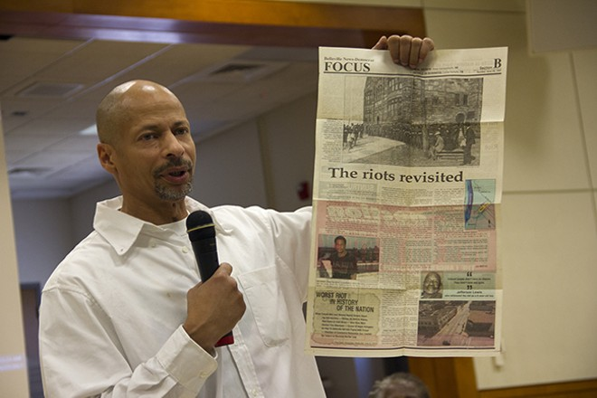 Dhati Kennedy holds up a 1997 newspaper story on the commemoration of the 80th anniversary of the 1917 violence. - PHOTO BY DANNY WICENTOWSKI