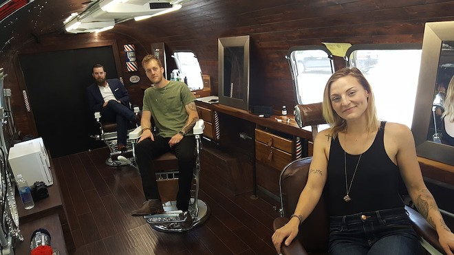 Jesse Goins, Frankie Petrillo and Cali Spencer relax in Dapper Den Grooming's barber chairs that are nearly 100 years old. - ALLISON BABKA