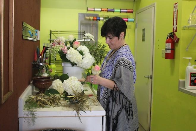 Elisheva Heit at work in her preferred medium: flowers. - PHOTO BY SARAH FENSKE
