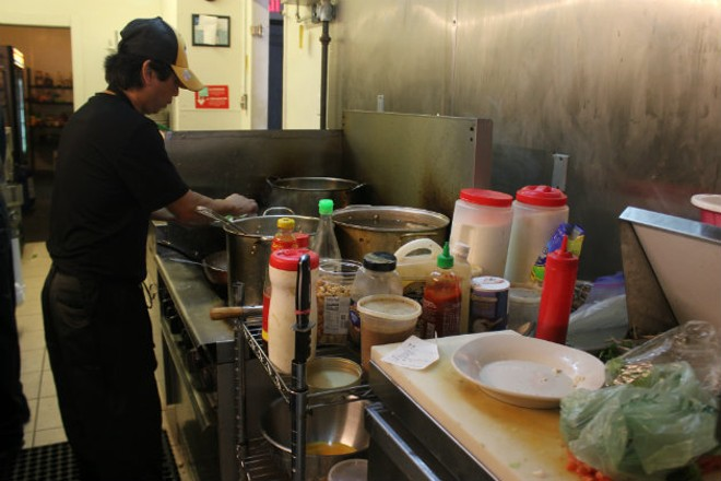 Owner MK Vongnarath hard at work in his small kitchen. - CHERYL BAEHR