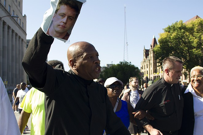 Activist Anthony Shahid brandishes a puppet with the face of former St. Louis cop Jason Stockley. - PHOTO BY DANNY WICENTOWSKI