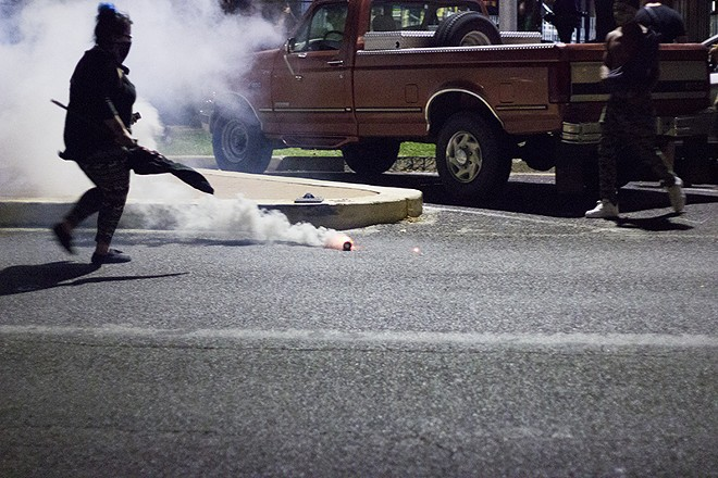 A protester prepares to kick a tear gas canister back to the police line. - PHOTO BY DANNY WICENTOWSKI