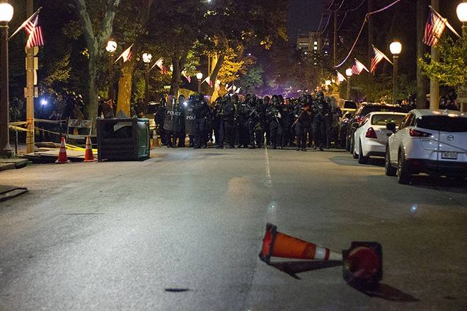 Officers marching down Euclid, shortly before deploying additional pepper balls and tear gas. - PHOTO BY DANNY WICENTOWSKI