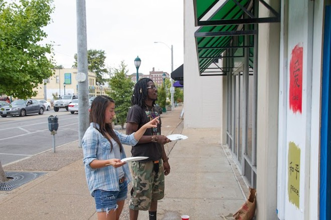 Artists Abby Wong and Saifullah Bin Khemet paint at Corner 17. - COURTESY OF PAINTING FOR PEACE IN FERGUSON, A CHILDREN'S BOOK