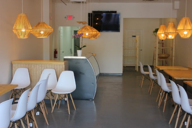 The interior is sleek and modern with white chairs, light-colored wood and bamboo pendant lights. - CHERYL BAEHR