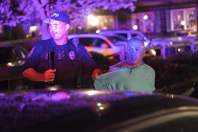Police apprehended this man after he swatted a journalist's camera. - PHOTO BY DANNY WICENTOWSKI