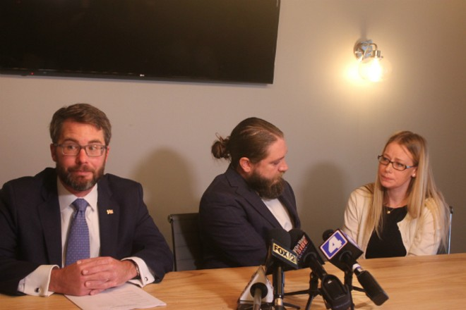 Drew and Jennifer Burbridge tell their story with their attorney Talmage E. Newton IV (right). - PHOTO BY DOYLE MURPHY