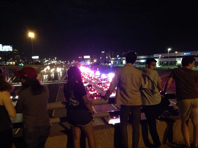 Bystanders watch from the bridge over I-64 as protesters march along the highway. - DOYLE MURPHY