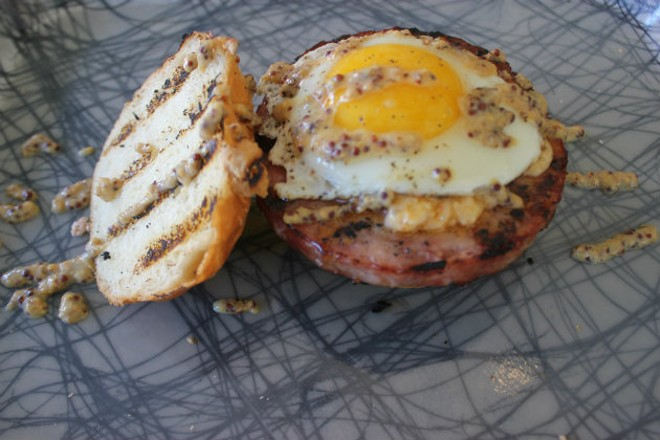 The housemade bologna sandwich is topped with an over-easy egg, pimento cheese and grain mustard. - CHERYL BAEHR