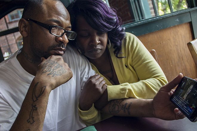 Danny Barnett and Nyeisha Muldrew watch a November KSDK news story of his arrest for the beating and robbery of Huan Le. - DANNY WICENTOWSKI
