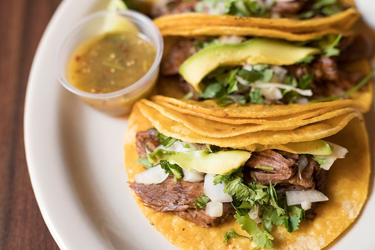 Tacos with slow-cooked beef, onions, cilantro and avocado.