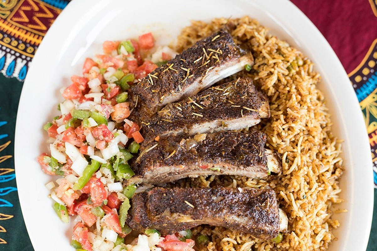 The half-rack of marinated fire-roasted pork, served here with kachumbali and rice, stands up to the best barbecue in St. Louis.