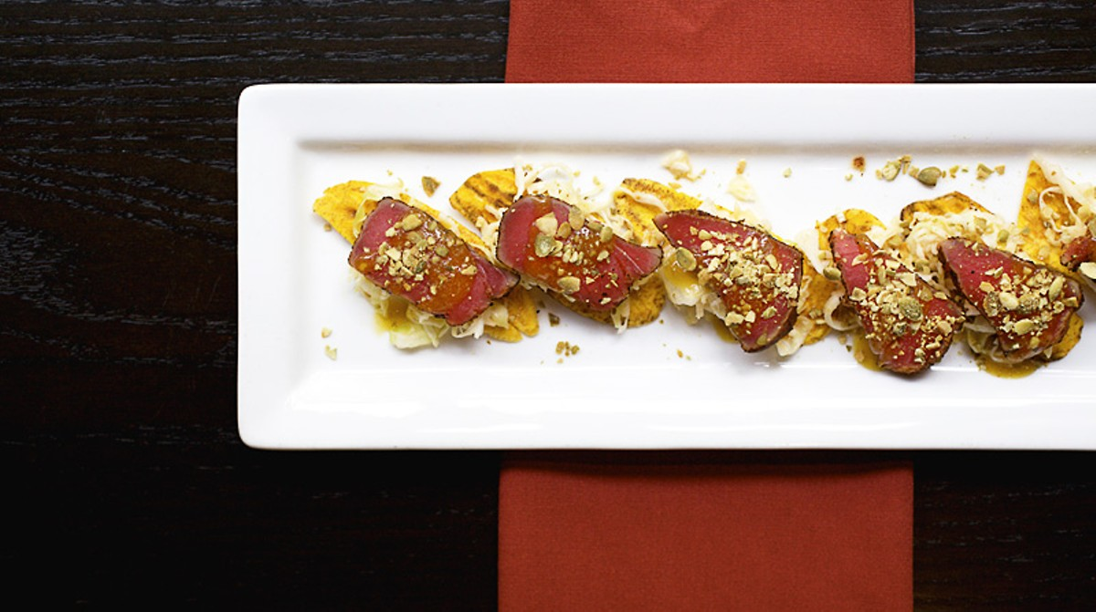 Ahi Tuna Tostadas, one of the �Fresh Beginnings� on the menu, is comprised of seared rare tuna with lime slaw, mango Habanero sauce and toasted pepitas on a crisped plantain chip. See more photos from inside Kota Wood Fire Grill.