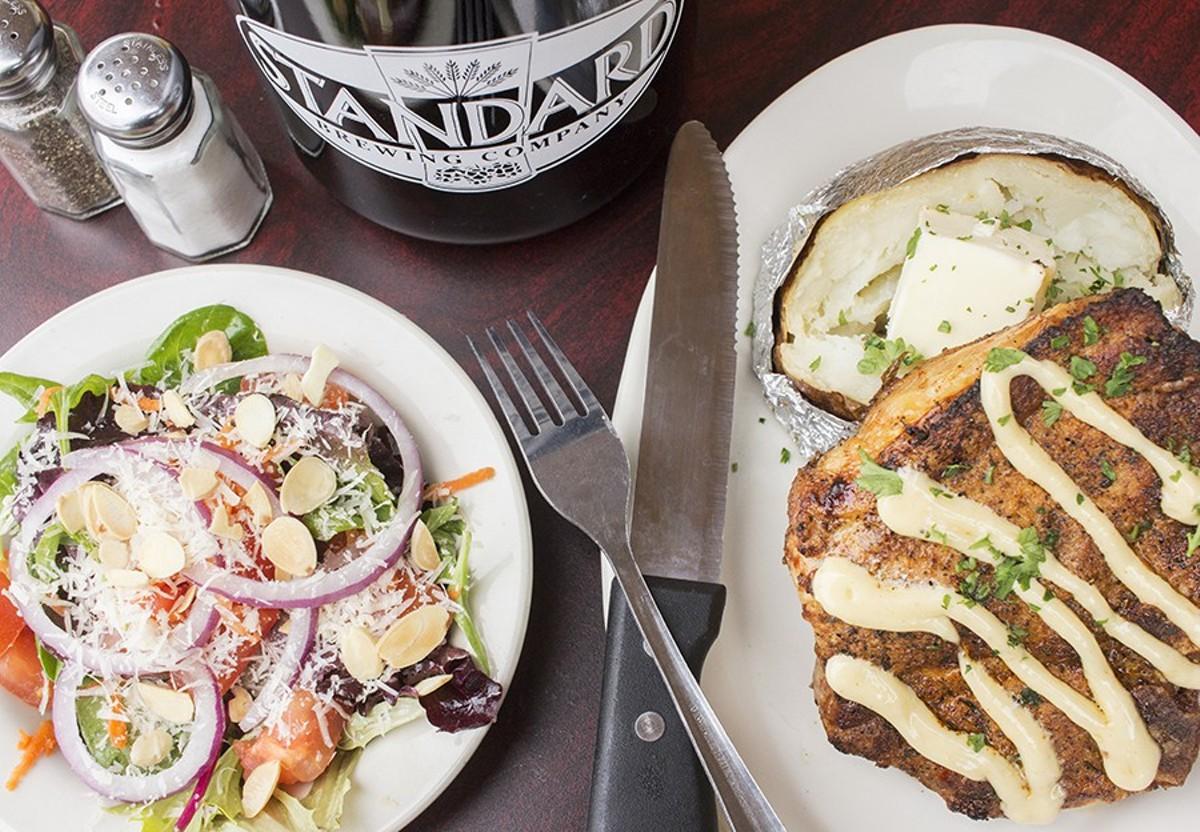 Standard Brewing Company's pork porterhouse, a 14-ounce blackened bone-in pork steak with roasted garlic aioli, a baked potato and a small house salad.