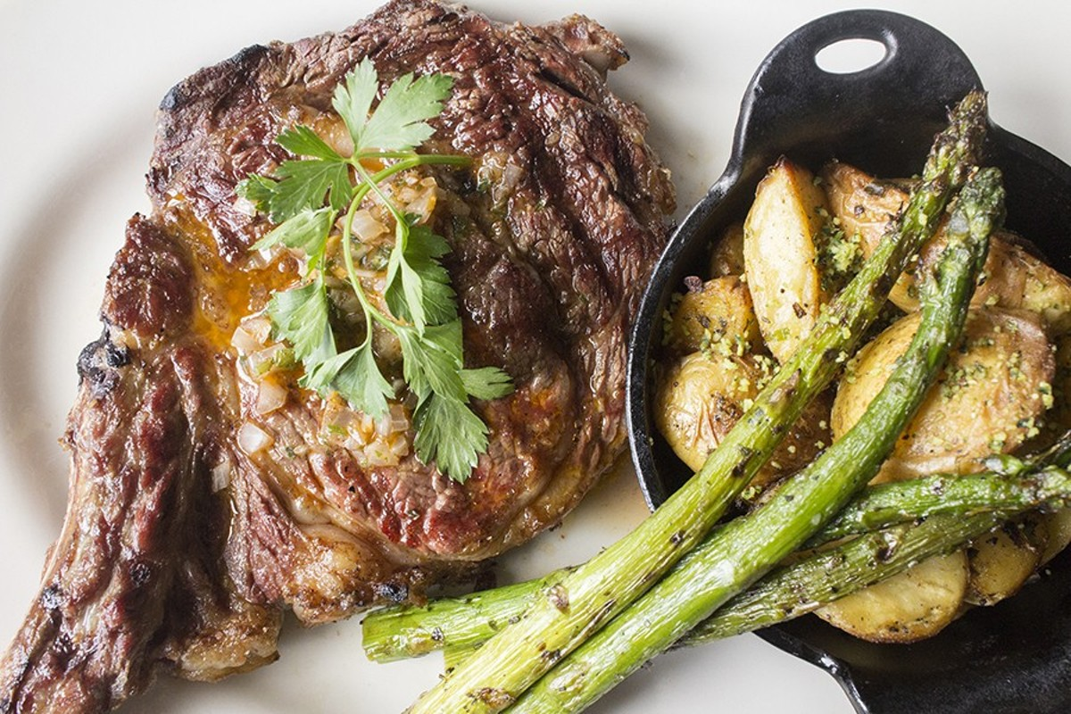 Weber Grill Restaurant's bone-in ribeye steak is served  with asparagus and potatoes.
