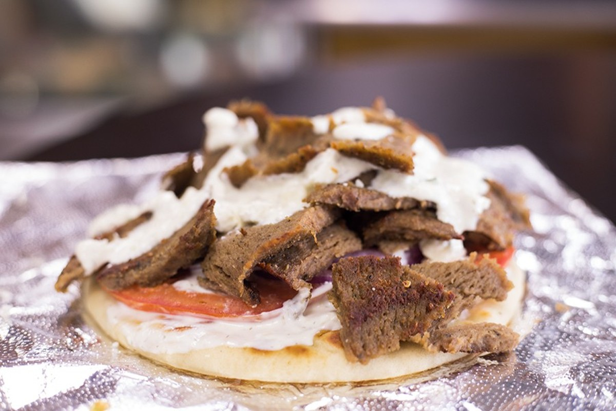 Gyro with lamb-beef combo on flat bread with tomato, red onion and tzatziki sauce.