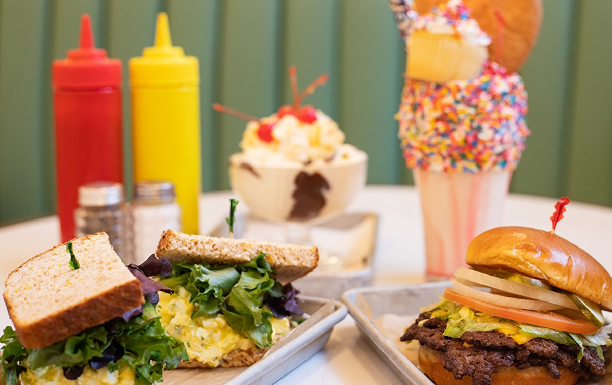 A selection of items from the Soda Fountain, pictured from left to right, top to bottom: egg salad sandwich, double cheeseburger, All-American Sundae and A Very Happy Un-Birthday Freak Shake.