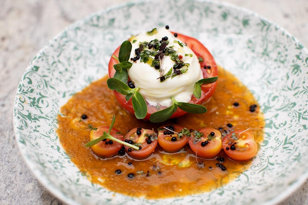 Tomato salad with burrata, tomato vinaigrette, basil, gremolata and balsamic caviar.