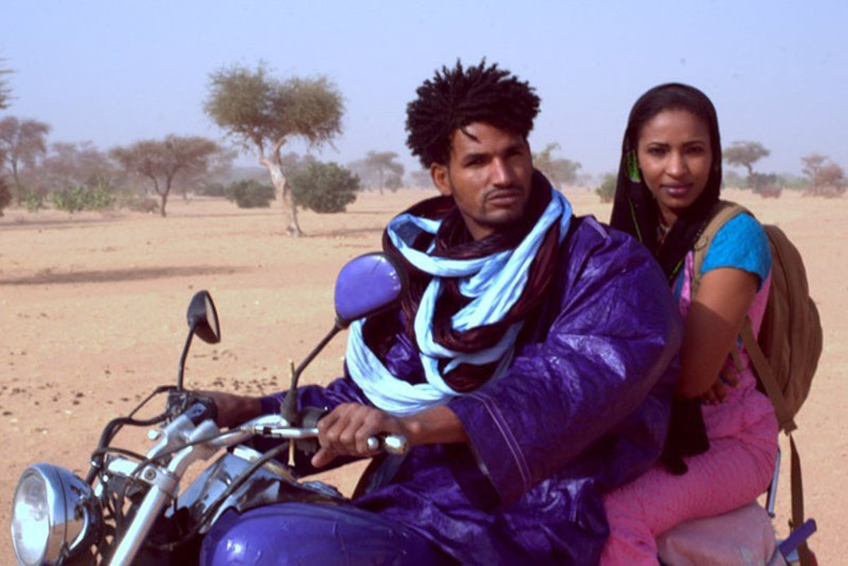 Mdou (Mdou Moctar) and Rhaicha (Rhaicha Ibrahim) race through the Sahara in Akounak Tedalat Taha Tazoughai.