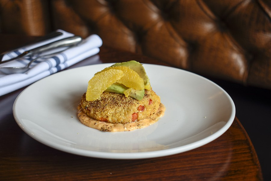 The lump crab cake is topped with avocado and blood orange. - KELLY GLUECK