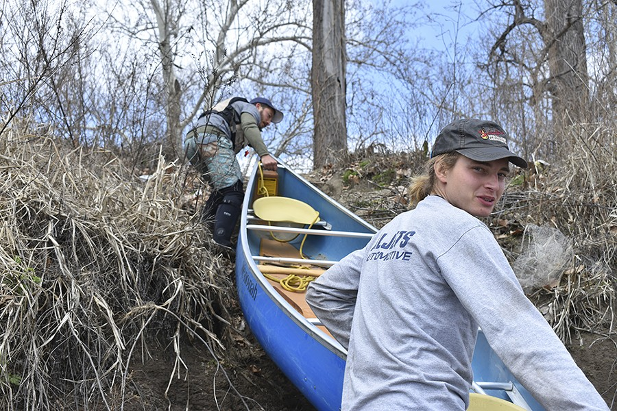 Paul Gruber, left, and Tanner Aljets of Big Muddy Adventures haul a canoe up a ten-foot embankment. - DOYLE MURPHY
