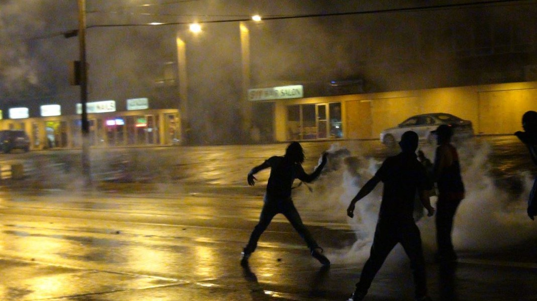 A protester throws a tear-gas canister back at the police who shot it. - RAY DOWNS
