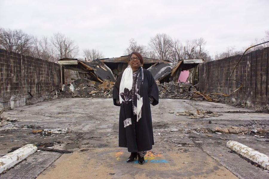 Juanita Morris stands in front of the remains of her store, Fashion R Boutique, which was burned down in the rioting over Michael Brown's death. - ALL PHOTOS BY DANNY WICENTOWSKI