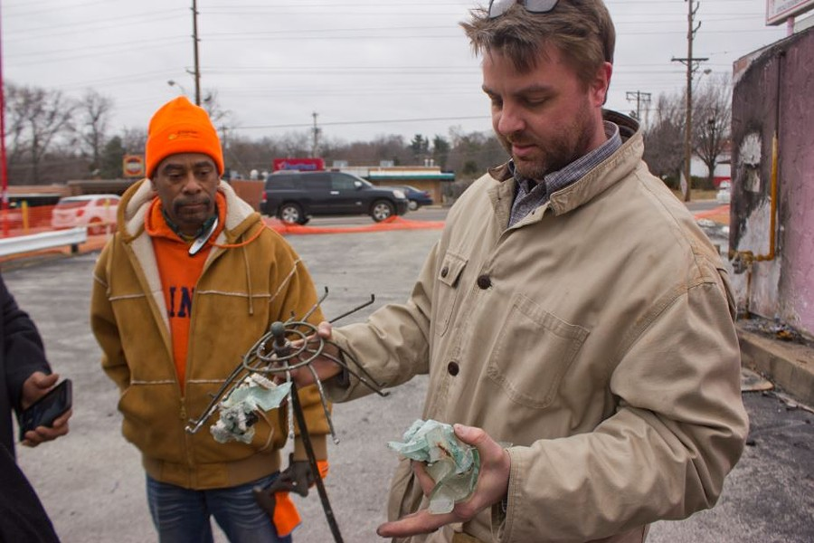 Jeff Meyer, the Missouri History Museum collections manager, holds up a hunk of melted glass and the remains of a parasol he found in the wreckage.