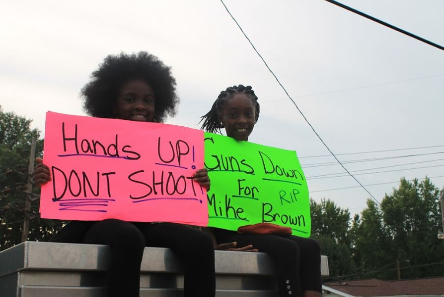 """Girls join a Ferguson protest with a """"Hands up, don't shoot"""" sign on August 14. - RAY DOWNS"""
