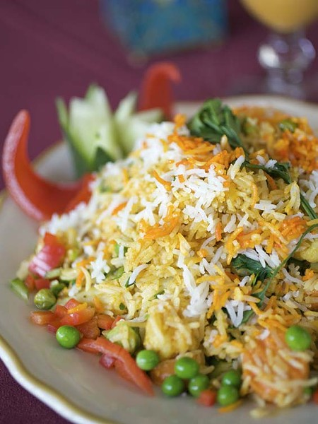 Vegetable biryani is saffron-flavored basmati rice prepared with cashews, almonds and raisins and, in this case, served with vegetables. See full slideshow here. - PHOTO: JENNIFER SILVERBERG