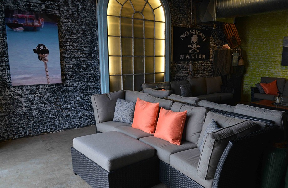 Massive arch windows and comfy couches help liven up the Rhone space which was once a gym and a factory before that. - TOM HELLAUER