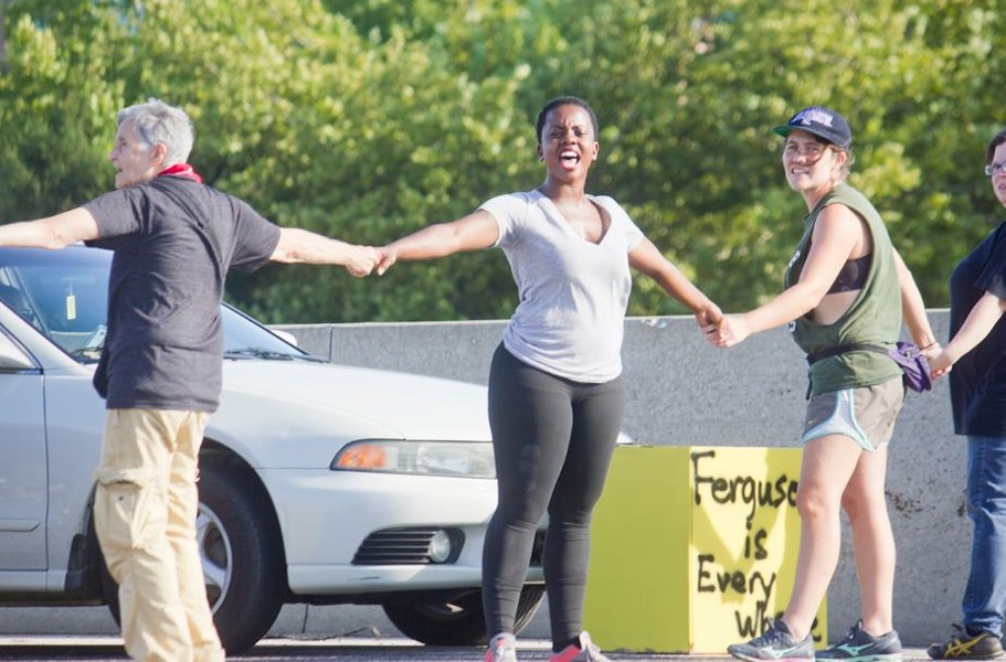 Brittany Ferrell, a cofounder of Millennial Activists United, lead protesters in chants while blocking I-70 on Monday. - DANNY WICENTOWSKI