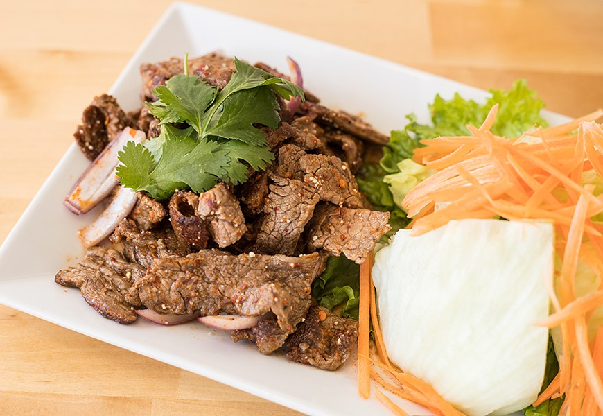 Nam Tok, or flame-grilled sliced beef, is tossed in a spicy lime dressing with toasted rice, red onions, green onions and cilantro. - MABEL SUEN