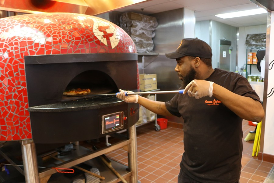 Termaine Rogers pulls a fresh pizza out of the oven. - CHELSEA NEULING