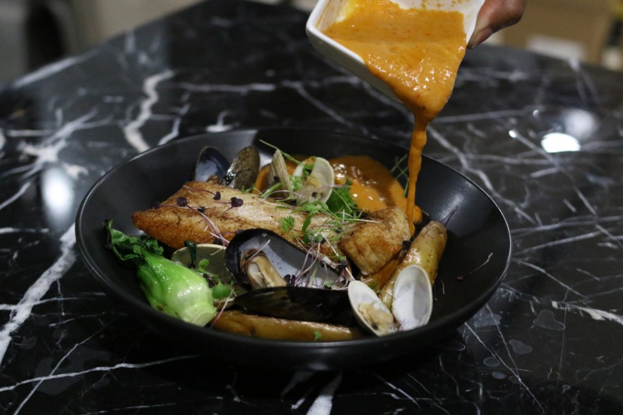 The sauce on the halibut is poured tableside, with littleneck clams, fingerling potatoes, baby bok choy and basil oil in a red curry. - CHELSEA NEULING