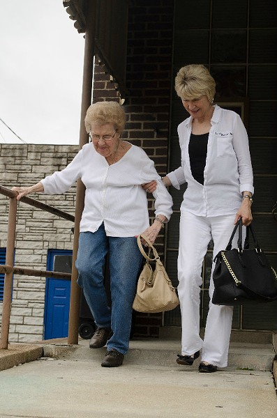 "Pam Moellenhoff leads her mother Marilyn, one of tavern's longest lasting patrons, down the Hilltop Inn's steps after the bar's final lunch. Lindsay Houser McHune, Moellenhoff's daughter, helped run the Hilltop during its final lunch as a part of her ""bucket list."" - KAVAHN MANSOURI"