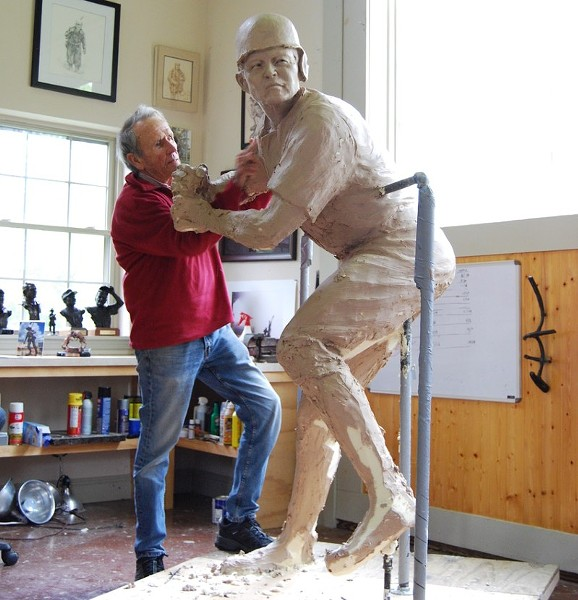 Sculptor Harry Weber perfects the sculpture of a Chinese baseball player. - HARRY WEBER