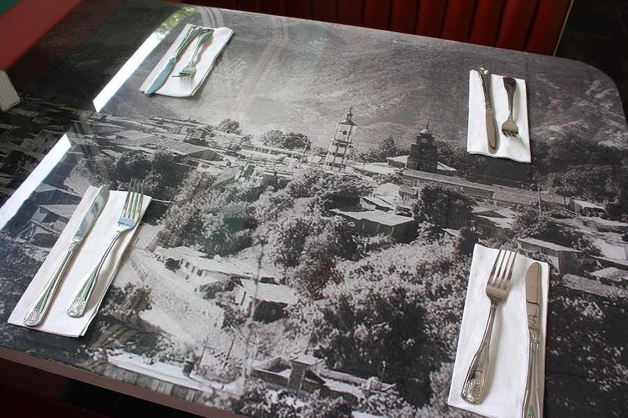 Old photos of the family's hometown decorate the tables, which were made by Veronica's son, Steve Suarez. - KATIE COUNTS