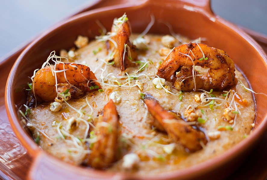 Prime 55's Cajun influence is most apparent in its shrimp and grits, served with blackened shrimp, popcorn grits and chile oil. - MABEL SUEN