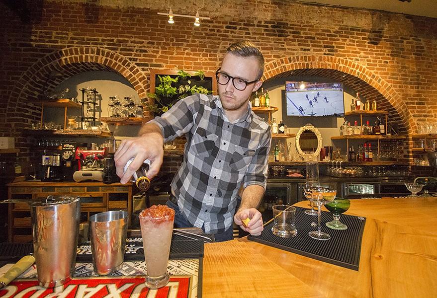 Bartender Tai Nalewajkó mixes drinks behind the bar. - PHOTO BY MABEL SUEN