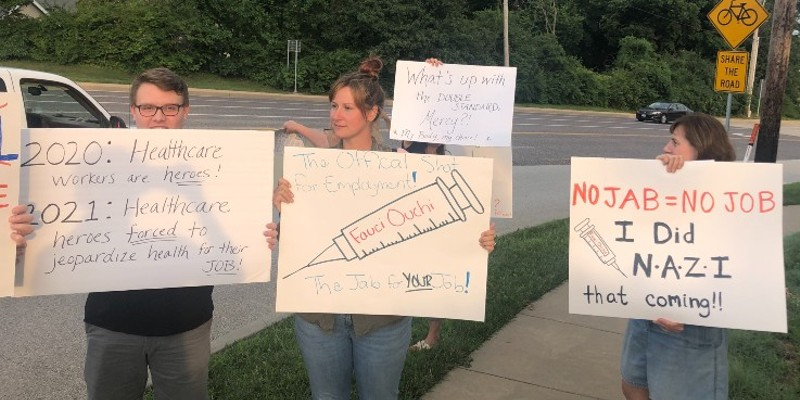 Protesters outside of Mercy Hospital St. Louis   on Sunday protest a policy to require employees to get vaccinated.